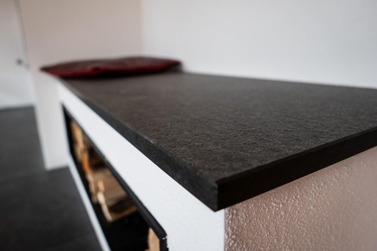 Heizkamin mit Ofenbank aus Naturstein und Regalfächern aus Stahl